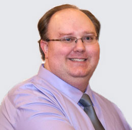 Photo of Eric Brockway, Lead Developer for Brukenet Web Development. He is dressed in a lavander dress shirt and silver tie.  He is clean-shaven, has short hair, and wears glasses.